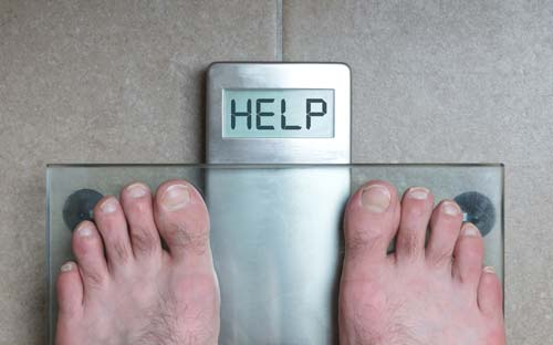 "Man's feet on scale with the word ""help"" showing as the weight"
