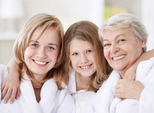 Three generations of women standing arm in arm