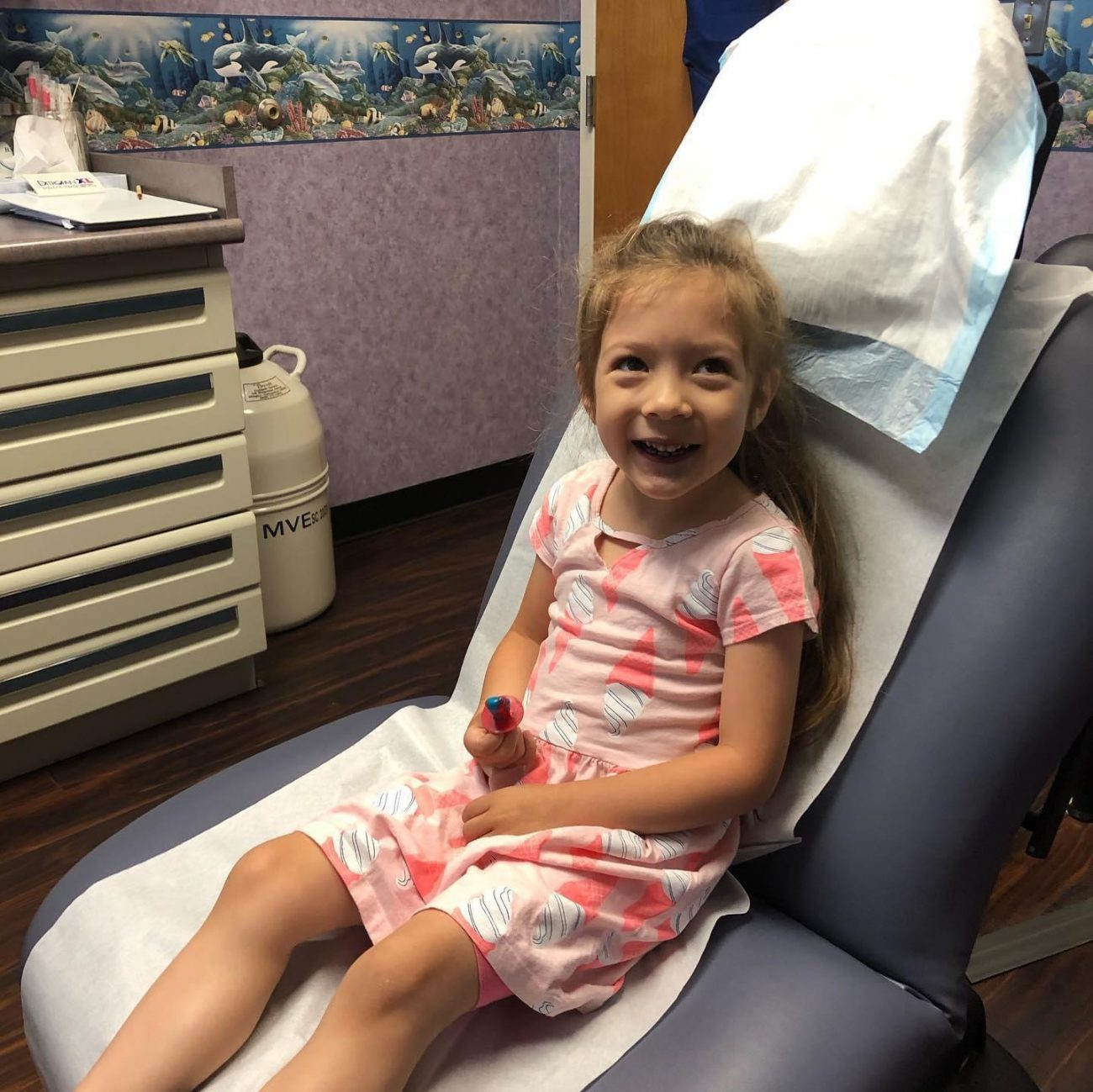 Little girl patient sits on exam chair and smiles