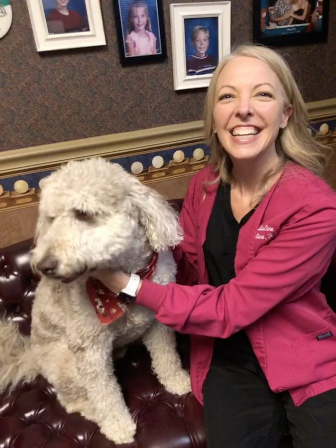Christine Myers smiling and petting fluffy white dog