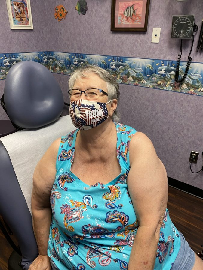Older woman in exam room wearing facemask