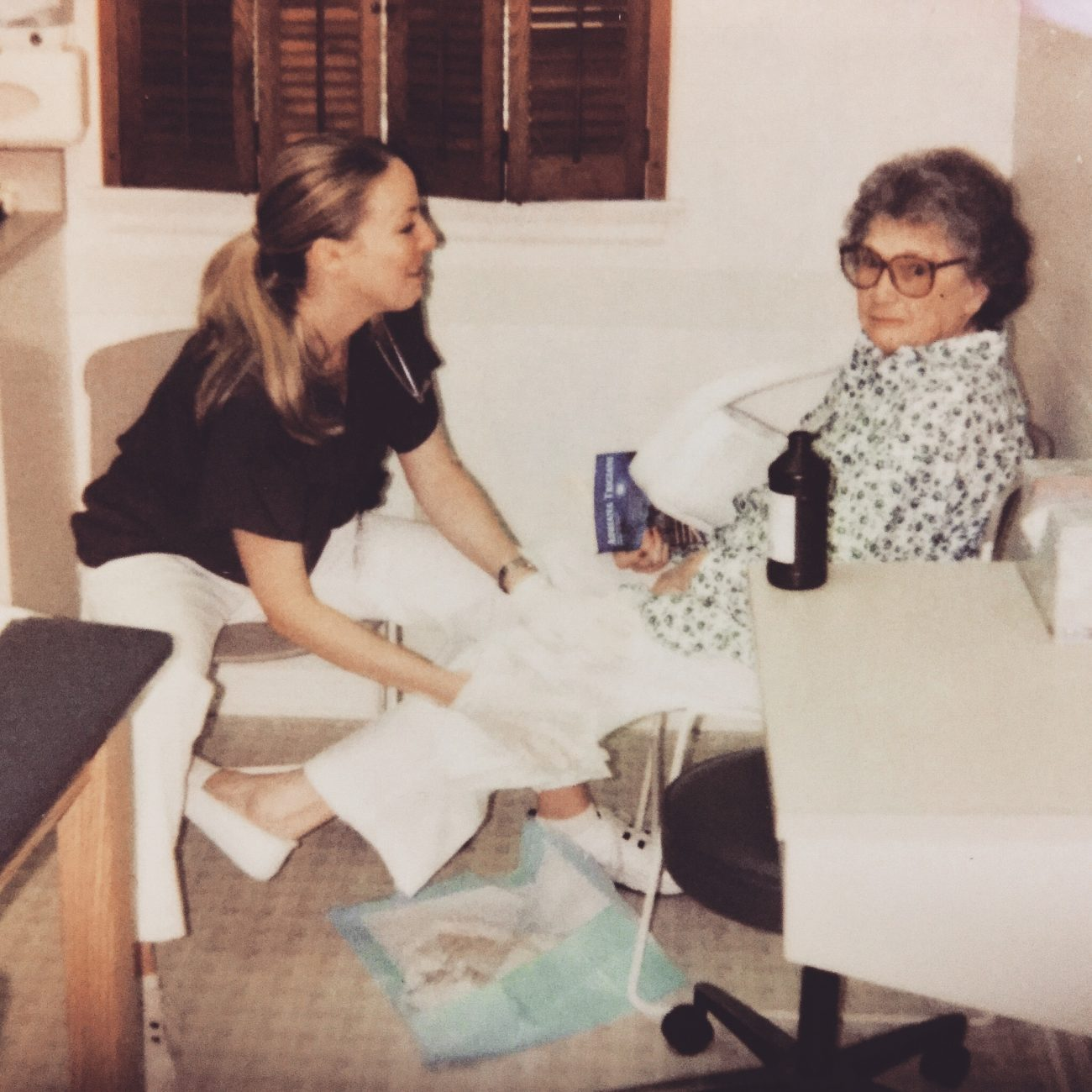 Older photo of staff member with elderly patient