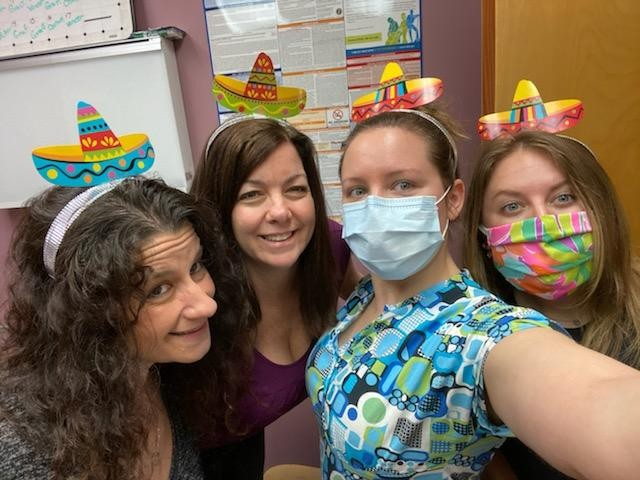 Seretis staff posing with paper sombreros on their heads